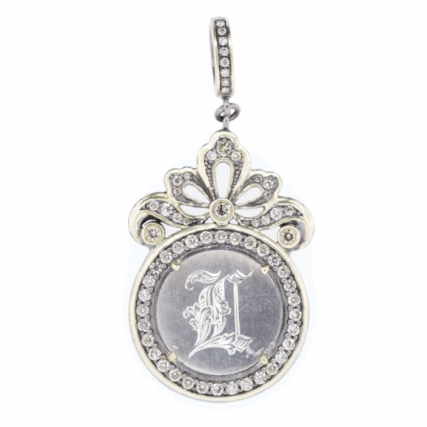 """Closeup photo of Love Token Engraved With """"L"""""""