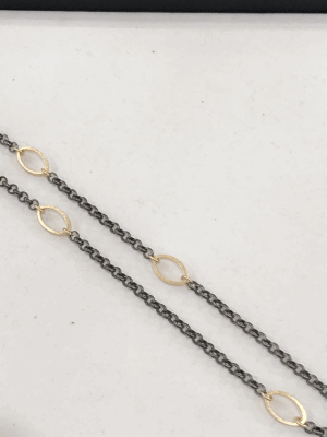 18k gold handmade charms are woven with tribal asymmetry to a black leather choker, evoking the feel and craft of ethnic handmade jewelry with elegance.