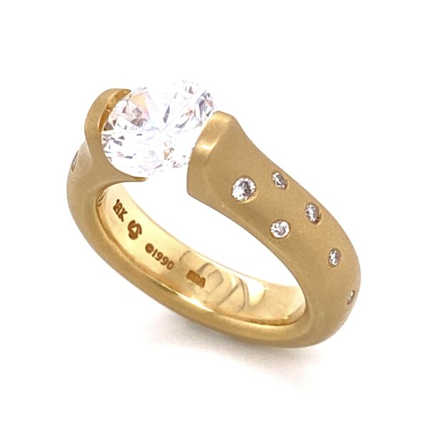 Closeup photo of Omega Round Engagement Ring with Scattered Melee for 1.5ct Round in Matte 18K Yellow Gold