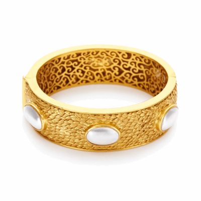 Hinged to fit all wrists, the Paradise Stone Hinge Bangle features six stone, pearl cabochons set in 24k gold feather-carved detail. Learn more: