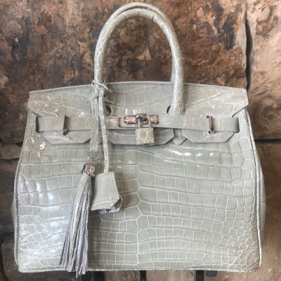 LaNae's Anna 30 is a top handle bag made of genuine saltwater crocodile skin. Proudly handcrafted in the USA by 3rd generation artisans, all edges are hand painted, interior is garment suede and is detailed with Italian palladium hardware. Each luxury bag may be fastened and locked with a key. The coordinating tassel and key may be removed. Each luxury bag is one of a kind and especially made for you to stand out against the crowd!