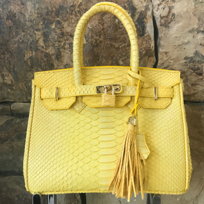 LaNae's Anna 30 is a top handle bag made of genuine python skin. Proudly handcrafted in the USA by 3rd generation artisans, all edges are hand painted, interior is garment suede and is detailed with Italian palladium hardware. Each luxury bag may be fastened and locked with a key. The coordinating tassel and key may be removed. Each luxury bag is one of a kind and especially made for you to stand out against the crowd!