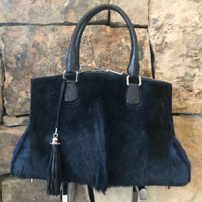 LaNae's Bell is a top handle bag made of genuine springbok and ostrich skin. Proudly handcrafted in the USA by 3rd generation artisans, all edges are hand painted, interior is garment suede and is detailed with Italian palladium hardware. The Bell's double zip opening is for easy access from the bottom of the bag to the very top. This style may be worn over the shoulder (comes with a strap to hook on two D rings). The interior has one zip pocket and one phone pocket. Also, detailed with a coordinating tassel. Each luxury bag is one of a kind and especially made for you to stand out against the crowd!