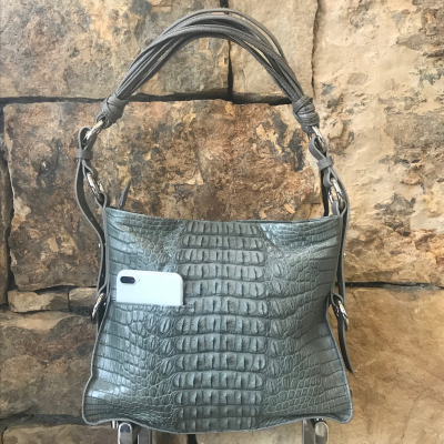 "LaNae's Amanda Over the Shoulder Handbag is made of genuine Nile Crocodile skin. Proudly handcrafted in the USA by 3rd generation artisans, all edges are hand painted, interior is garment suede and is detailed with Italian palladium hardware. It comes with an over the shoulder strap extending to 20"". The interior is complete with one zippered and two open pockets. The cell phone pocket on the outside of the handbag is super convenient! The strap drop is 10"". Each luxury bag is one of a kind and especially made for you to stand out against the crowd!"