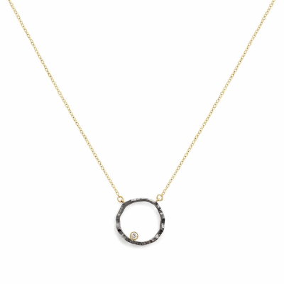 "A surrealist interpretation of an open circle, the Open Silhouette Necklace features a hammered finish and a diamond placed off-center. The playful, elegant simplicity of this necklace makes it wearable for a woman of any age, for every day or for any occasion.  Available in all 18 karat yellow gold or in a combination of 18 karat yellow gold with black -rhodium plated sterling silver or 18 karat rose gold charm.  Features a .05 carat diamond. > 1g, 1.5cm diameter.  18k yellow gold 18"" chain length. Made in New York City from the world's finest materials and a ethically-sourced diamond. Please allow 3-4 weeks for delivery as each piece is made just for you."