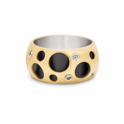 The Hollow Ring, one of Dana's first designs, consists of two connected rings, the outer of which features diamonds and circular cutouts of varying sizes to show off the contrast of colors.  Available in 18 karat yellow gold exterior with black rhodium-plated sterling silver interior with white diamonds or in Sterling Silver exterior with 18k yellow gold plated interior with black diamonds.  Features eight white diamonds, burnish set into the ring's holes, approx. 0.25 carats. 1 cm, 11 g. Please inquire about ring sizes not listed, sales@danabronfman.com  Made in New York City from the world's finest materials and ethically-sourced diamonds. Please allow 3-4 weeks for delivery as each piece is created specially for you.