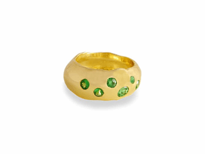 Our beloved 18K gold galaxy ring has a constellation of 7 sparkling green Tsavorite stones set in a band with natural molten details around the edges. Cast from an ancient Ethiopian gypsy ring, we have left the organic state of the metal to shine through.