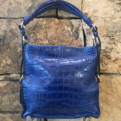 "LaNae's Amanda Over the Shoulder Handbag is made of genuine alligator skin. Proudly handcrafted in the USA by 3rd generation artisans, all edges are hand painted, interior is garment suede and is detailed with Italian palladium hardware. It comes with an over the shoulder strap extending to 20"". The interior is complete with one zippered and two open pockets. The cell phone pocket on the outside of the handbag is super convenient! The strap drop is 10"". Each luxury bag is one of a kind and especially made for you to stand out against the crowd! Fading has occured on this skin. Last two photos show fading. Call for more info."