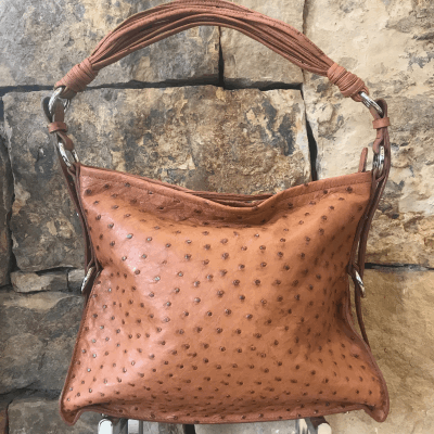 """LaNae's Amanda Over the Shoulder Handbag is made of genuine ostrich skin. Proudly handcrafted in the USA by 3rd generation artisans, all edges are hand painted, interior is garment suede and is detailed with Italian palladium hardware. It comes with an over the shoulder strap extending to 20"""". The interior is complete with one zippered and two open pockets. The cell phone pocket on the outside of the handbag is super convenient! The strap drop is 10"""". Each luxury bag is one of a kind and especially made for you to stand out against the crowd!"""