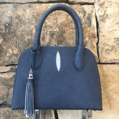 """LaNae's Small Dome is a top handle bag made of genuine stingray skin. Proudly handcrafted in the USA by 3rd generation artisans, all edges are hand painted, interior is garment suede and is detailed with Italian palladium hardware. This classic style comes with a fun tassel that can be detached. The interior has a zippered and a cell phone pocket. Under the handles are D rings to attach the over the shoulder strap (up to 25""""). Each luxury bag is one of a kind and especially made for you to stand out against the crowd!"""