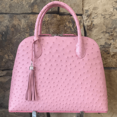 LaNae's Large Dome is a top handle bag made of genuine ostrich skin. Proudly handcrafted in the USA by 3rd generation artisans, all edges are hand painted, interior is garment suede and is detailed with Italian palladium hardware. This classic style comes with a fun tassel that can be detached. The interior has a zippered and a cell phone pocket. Under the handles are D rings to attach the over the shoulder strap. Each luxury bag is one of a kind and especially made for you to stand out against the crowd!