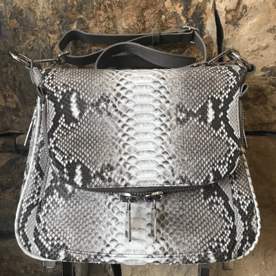 """LaNae's Zippered Messenger Handbag is made of genuine python and ostrich skin. Proudly handcrafted in the USA by 3rd generation artisans, all edges are hand painted, interior is garment suede and is detailed with Italian palladium hardware. The bottom zipper allows you to extend the size of the handbag. The fold over top has a zipper that can access a large private pocket that reaches to the bottom of the bag. The interior also has a zippered pocket and a cell phone pocket. The last pocket is under the fold over top for each access. It's complete with a adjustable 20"""" over the shoulder strap. Each luxury bag is one of a kind and especially made for you to stand out against the crowd!"""