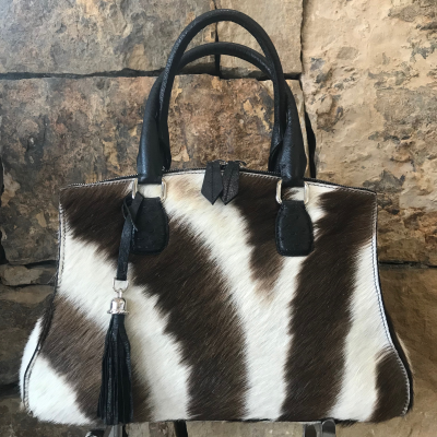 LaNae's Bell is a top handle bag made of genuine zebra skin. Proudly handcrafted in the USA by 3rd generation artisans, all edges are hand painted, interior is garment suede and is detailed with Italian palladium hardware. The Bell's double zip opening is for easy access from the bottom of the bag to the very top. This style may be worn over the shoulder (comes with a strap to hook on two D rings). The interior has one zip pocket and one phone pocket. Each luxury bag is one of a kind and especially made for you to stand out against the crowd!