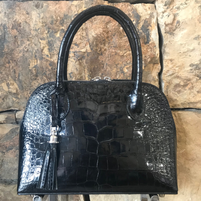 "LaNae's Small Dome is a top handle bag made of genuine alligator skin. Proudly handcrafted in the USA by 3rd generation artisans, all edges are hand painted, interior is garment suede and is detailed with Italian palladium hardware. This classic style comes with a fun tassel that can be detached. The interior has a zippered and a cell phone pocket. Under the handles are D rings to attach the over the shoulder strap (up to 25""). Each luxury bag is one of a kind and especially made for you to stand out against the crowd!"