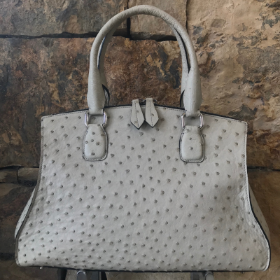 LaNae's Bell is a top handle bag made of genuine ostrich skin. Proudly handcrafted in the USA by 3rd generation artisans, all edges are hand painted, interior is garment suede and is detailed with Italian palladium hardware. The Bell's double zip opening is for easy access from the bottom of the bag to the very top. This style may be worn over the shoulder (comes with a strap to hook on two D rings). The interior has one zip pocket and one phone pocket. Each luxury bag is one of a kind and especially made for you to stand out against the crowd!