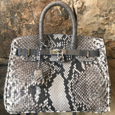 LaNae's Anna 30 is a top handle bag made of genuine python and ostrich skin. Proudly handcrafted in the USA by 3rd generation artisans, all edges are hand painted, interior is garment suede and is detailed with Italian palladium hardware. Each luxury bag may be fastened and locked with a key. The coordinating lock and key may be removed. Each luxury bag is one of a kind and especially made for you to stand out against the crowd!