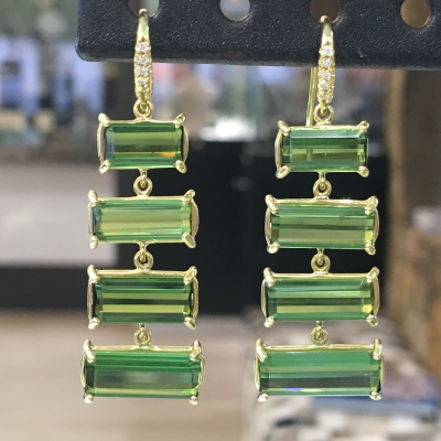 Lauren K's exceptional design and craftmanship is seen in these transleucent green tourmaline waterfall earrings. Four tourmaline stones per earring cascade from small to large and are set in 18K yellow gold. GreenTourmaline: 15.88cts Diamond: 0.07cts