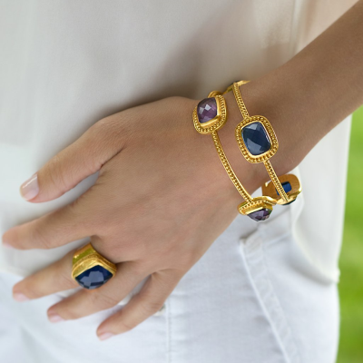 Available with either amethyst purple or sapphire blue imported rose-cut glass variations, the 24k gold plate Luxor Bangle is strikingly detailed. Shop today: