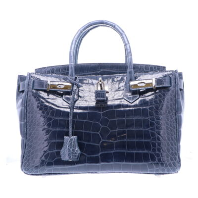 LaNae's Anna 30 is a top handle bag made of genuine alligator and ostrich skin. Proudly handcrafted in the USA by 3rd generation artisans, all edges are hand painted, interior is garment suede and is detailed with Italian palladium hardware. Each luxury bag may be fastened and locked with a key. The coordinating tassel and key may be removed. Each luxury bag is one of a kind and especially made for you to stand out against the crowd!